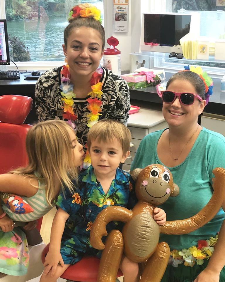 Kidzdent team members smiling with two pediatric dentistry patients