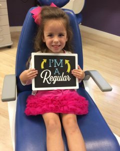 Pediatric Dentistry patient smiling holding a I'm a Regular sign