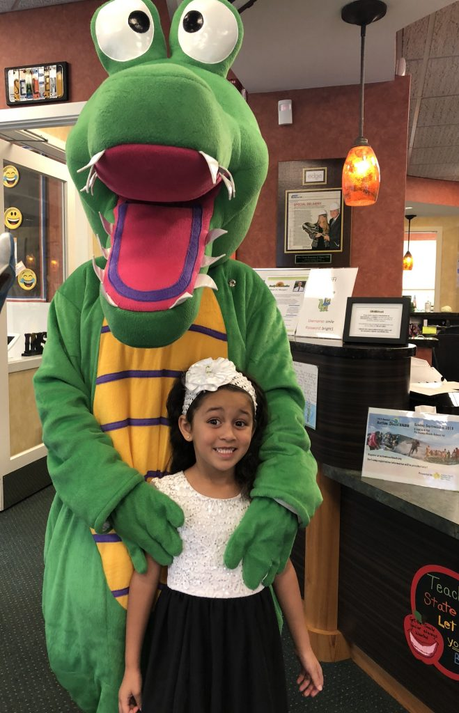 The Kidzdent mascot posing with a pediatric patient