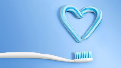 Toothpaste in the shape of a heart and a toothbrush