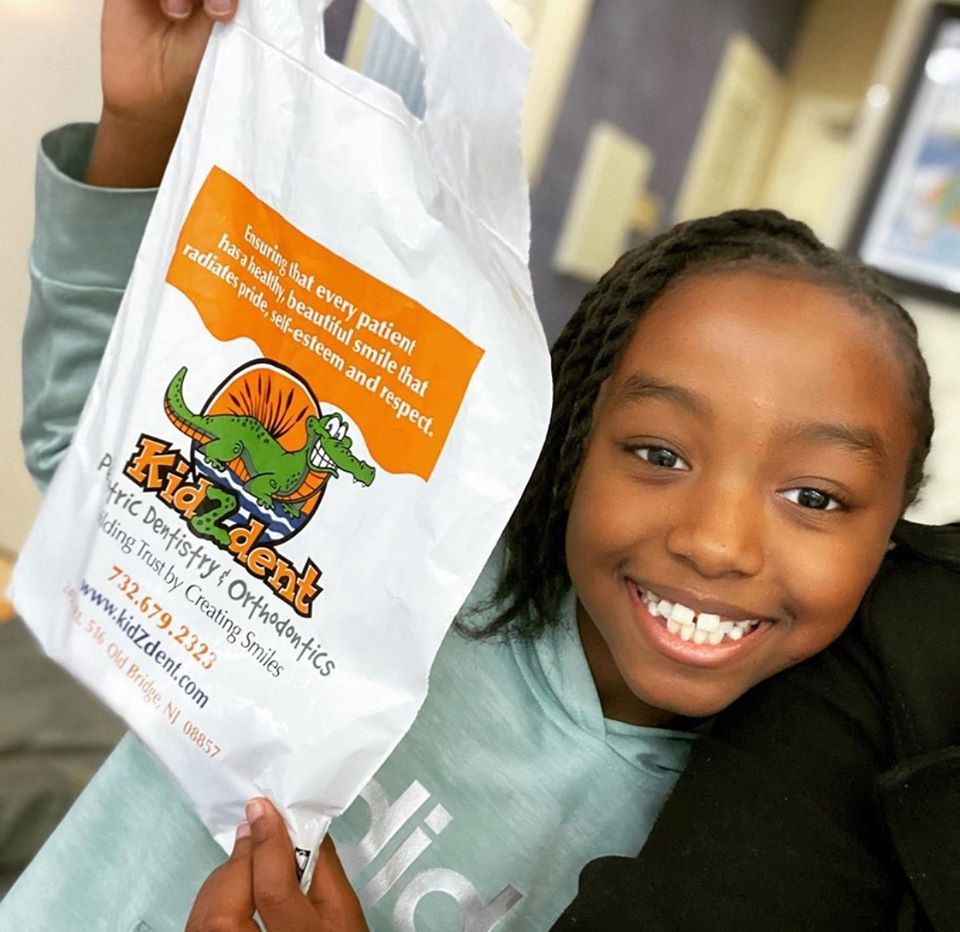 Kidzdent patient smiling with a tote bag after a successful IV sedation appointment